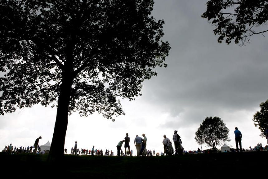 Golfers wait on the putting green as play is suspended due to rain in the final round of the PGA Tour's Barbasol Championship at Keene Trace Golf Club in Nicholasville, Kentucky, on July 22, 2018.