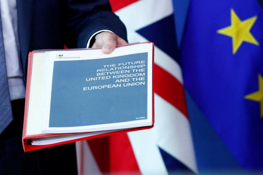 Britain's Secretary of State for Exiting the European Union Dominic Raab holds documents ahead of a meeting with European Union's chief Brexit negotiator Michel Barnier in Brussels on July 19, 2018.