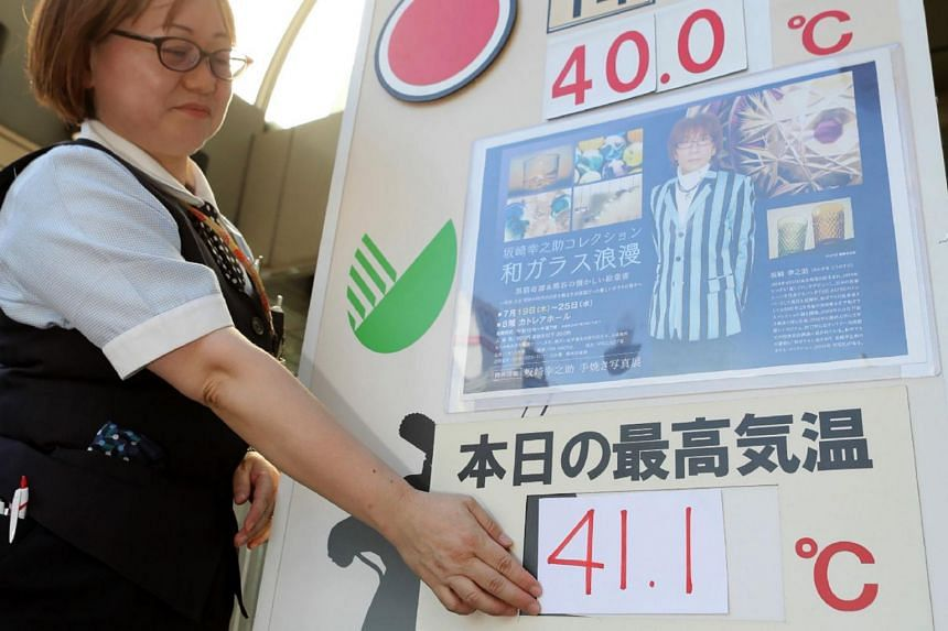 A department store employee places numbers showing a temperature of 41.1 deg C on a large thermometer board in Kumagaya, Saitama prefecture, on July 23, 2018.