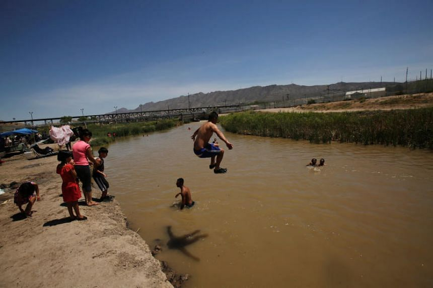 People cool themselves in the waters of the Rio Bravo, which divides Mexico and the US, during a hot summer day in Ciudad Juarez, Mexico, on July 22, 2018.