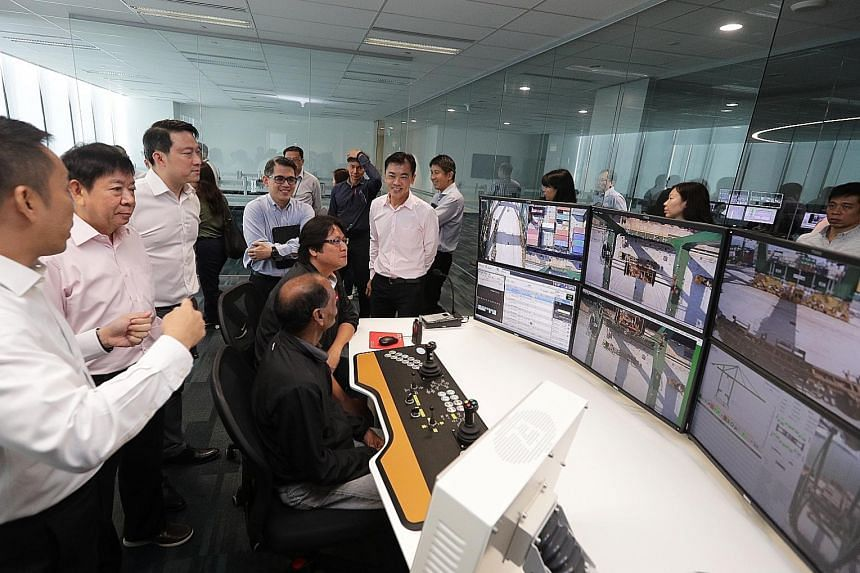 Transport Minister Khaw Boon Wan (second from left) and Dr Lam Pin Min (third from left), Senior Minister of State for Transport, were briefed at the Automated Crane Operations Centre on the new automated quay crane system at the Pasir Panjang Termin