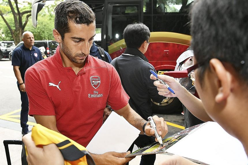 Above: Armenia midfielder Henrikh Mkhitaryan, who joined Arsenal from Manchester United in January, signing autographs. Right: A group of fans waiting for the Gunners to arrive at the Shangri-La hotel.
