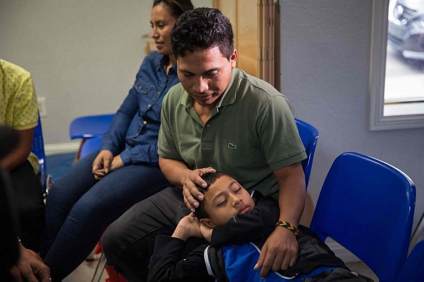 File photo showing an immigrant from El Salvador and his 10-year-old son at a Catholic Charities relief center. The children of more than 450 deported immigrant parents have been left behind in the US.