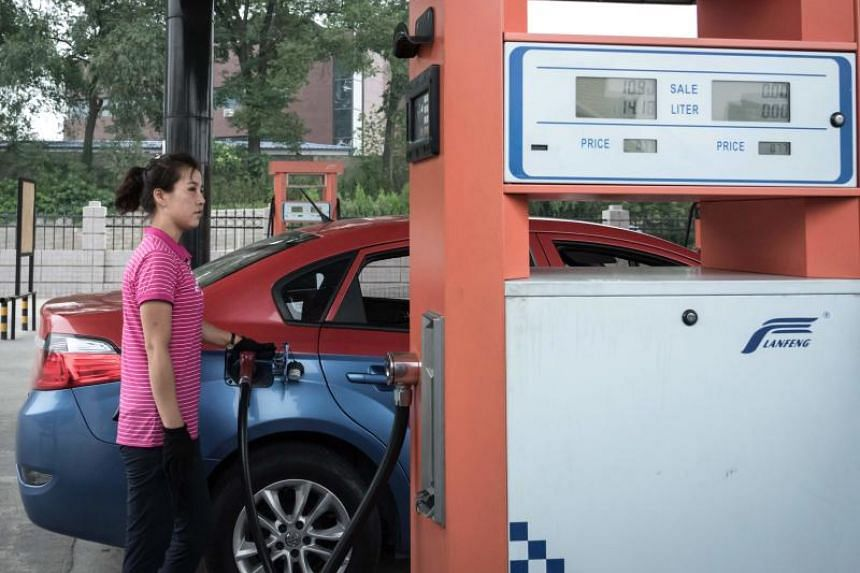 A file photo taken on July 21, 2017, shows a petrol pump attendant filling up a taxi with petrol at a fuel station in Pyongyang.