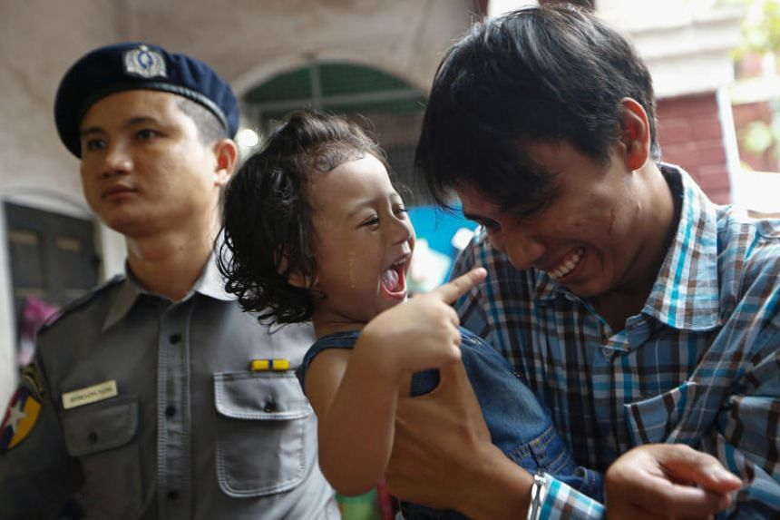Detained Reuters journalist Kyaw Soe Oo plays with his daughter as he is escorted by police at Insein court in Yangon on July 24, 2018.
