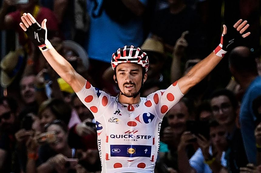 France's Julian Alaphilippe, wearing the best climber's polka dot jersey, celebrates as he crosses the finish line.