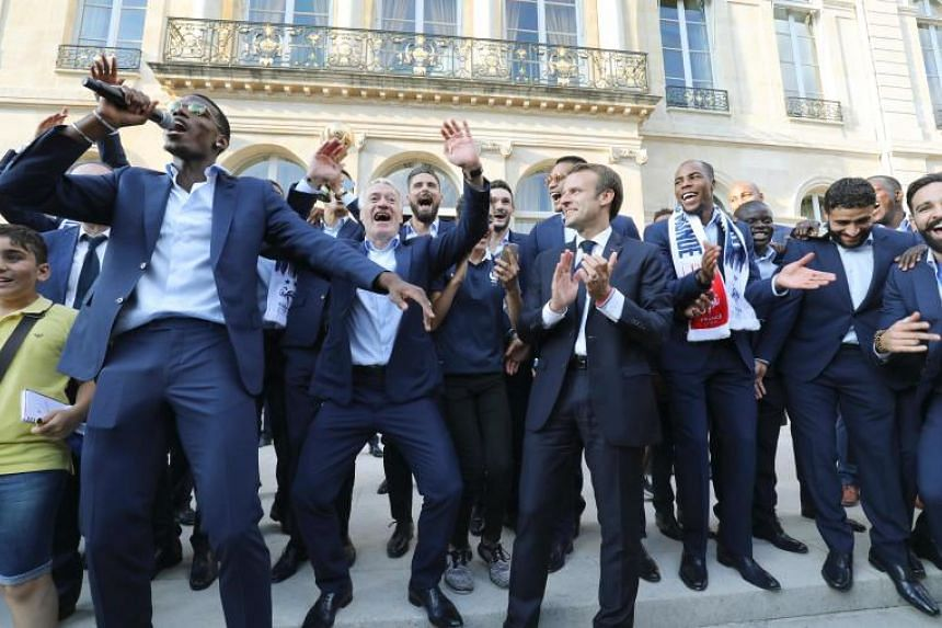 French national football players celebrate winning the World Cup with French President Emmanuel Macron during a reception at the Elysee Presidential Palace in Paris on July 16, 2018.