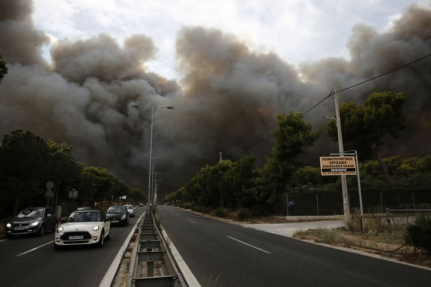 Smoke rising over an avenue during a forest fire in Neo Voutsa, a northeast suburb of Athens, Greece, on July 23, 2018.