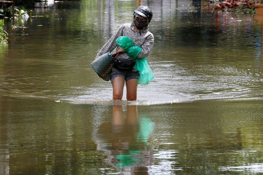 A woman wades through a flooded village after heavy rainfall caused by tropical storm Son Tinh in Ninh Binh province, Vietnam, on July 22, 2018.
