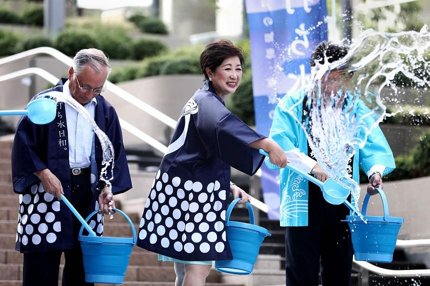 Tokyo Governor Yuriko Koike splashing water on the ground during a water sprinkling event called Uchimizu to cool down the area, in Tokyo. New warnings have been issued as a deadly heatwave blankets Japan.