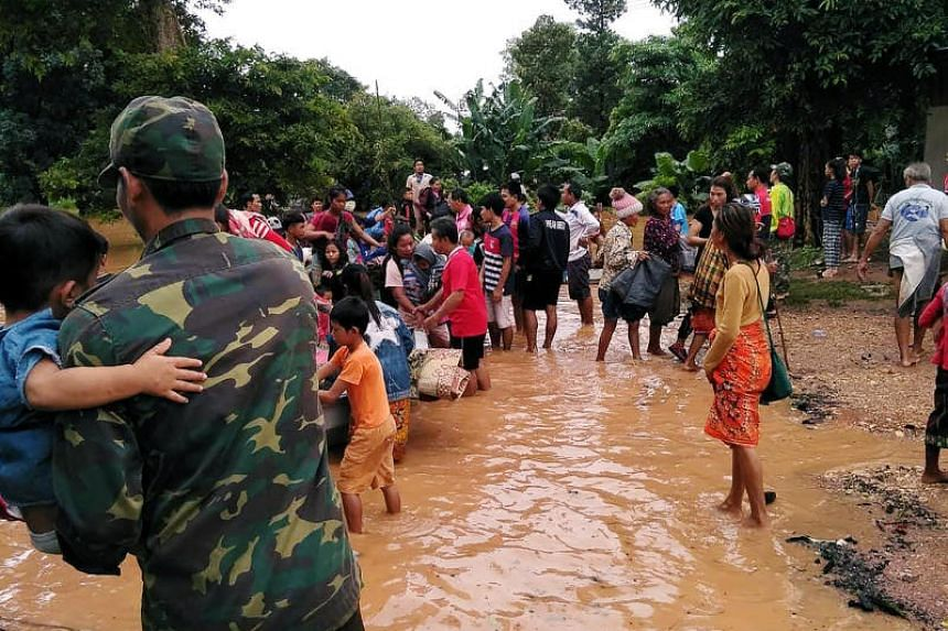 Villagers carry their belongings as they evacuate after the Xepian-Xe Nam Noy hydropower dam collapsed in Attapeu province, Laos, on July 24, 2018.