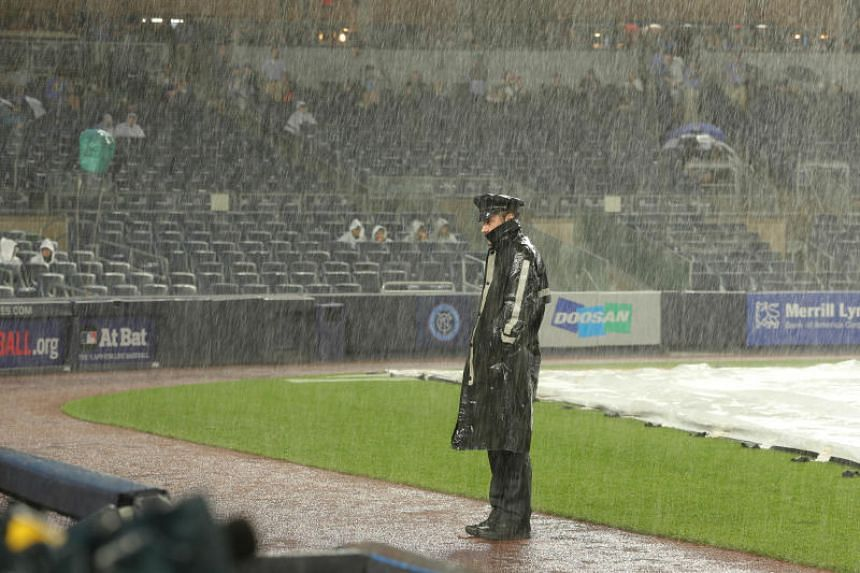 A police officer stands on the field during a rain delay before the game between the New York Yankees and the New York Mets at Yankee Stadium in New York on July 22, 2018.