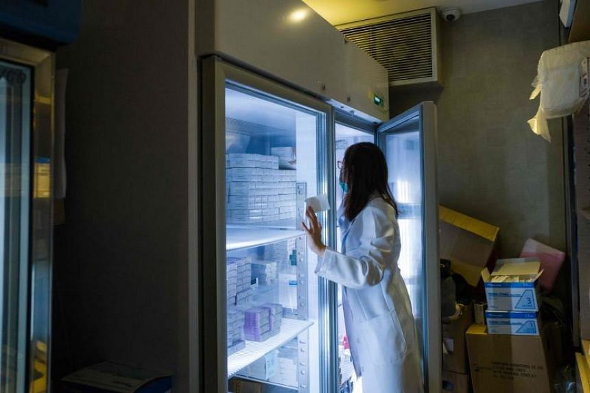 A nurse looks for vaccines in a fridge at a private clinic that performs vaccinations in Hong Kong on July 24, 2018.
