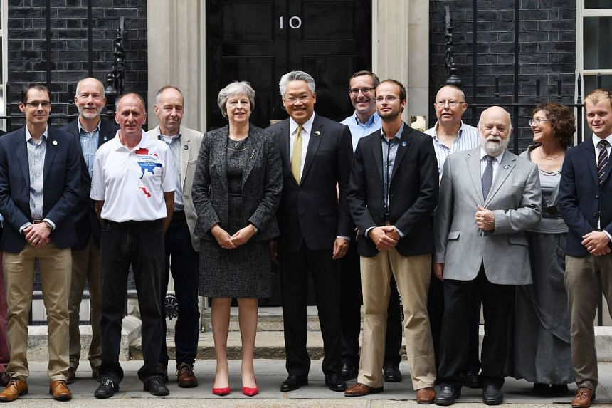 May and Mr Pisanu Suvanjata welcome the divers and their support team to Downing Street in London.