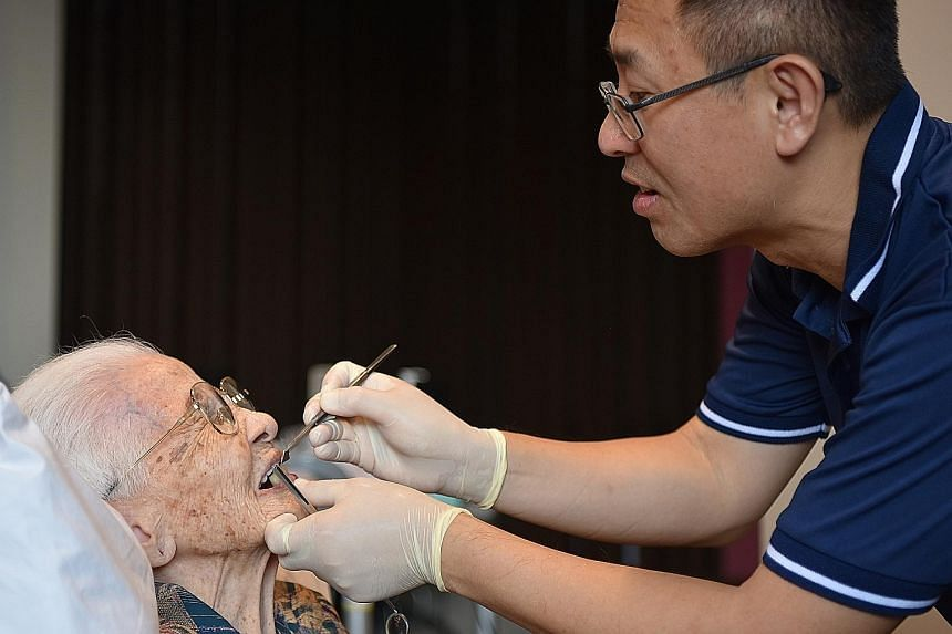 Madam Liew Yao Tai, 98, a resident of St Joseph's Home, having her dentures fitted by dentist Au Eong Kah Chuan, 50, on Sunday. He is among 20 dentists from the Humanitarian With Love group's dental section who visit the home once a month to provide