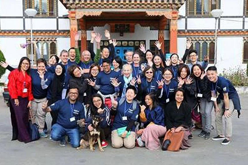 Above: Volunteers from Bhutan, China, India, Japan, Singapore, Britain and the US on Smile Asia's Screening Day outside Paro Hospital, Bhutan, in October 2016. Left: Eight-month-old Tandin Tshomo with her mother, Ms Sangay Lhamo, 19, and father, Mr S