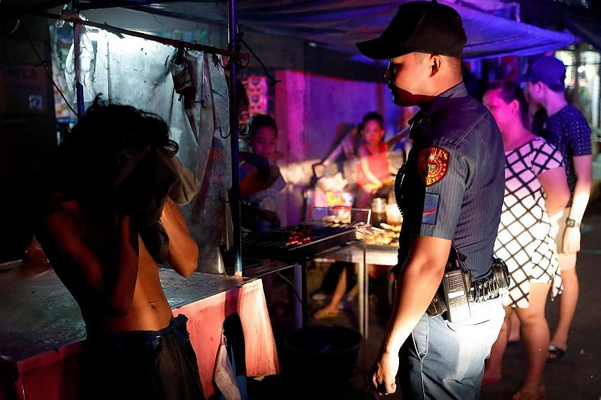 A police officer interrogating a shirtless man during an anti-loitering night patrol in Manila early this month. Men found shirtless, and those smoking or drinking alcohol outdoors, are taken to district offices, where they are cautioned and their na