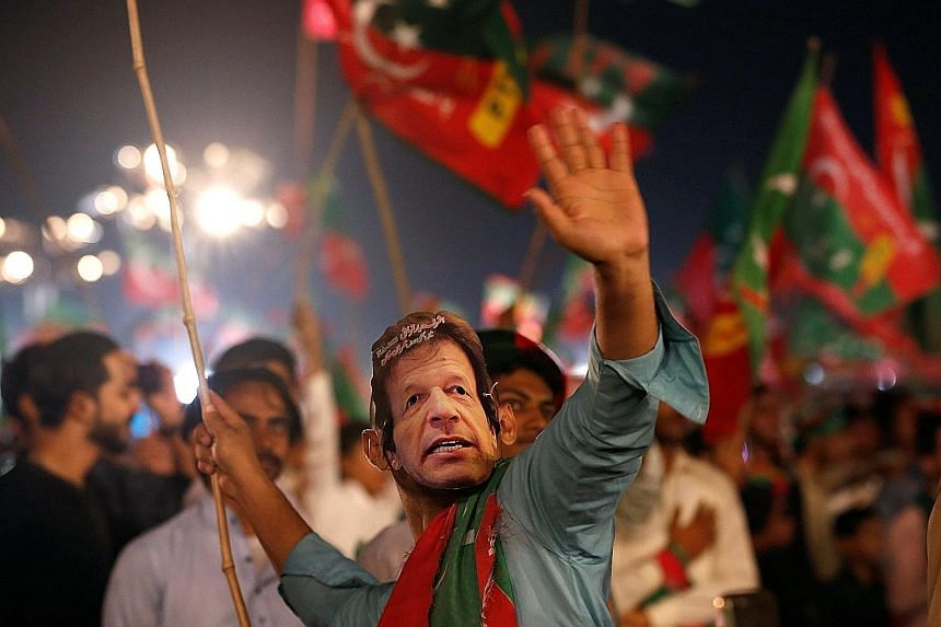 """A supporter of Mr Imran Khan, wearing an """"Imran Khan"""" mask during a campaign rally on Sunday ahead of today's general election in Karachi, Pakistan."""