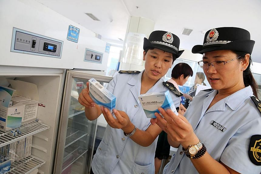 China Food and Drug Administration officials checking rabies vaccines at the Disease Control and Prevention Centre in Anhui province yesterday. The Chinese authorities are scrambling to defuse public outrage over a safety scandal involving vaccines.