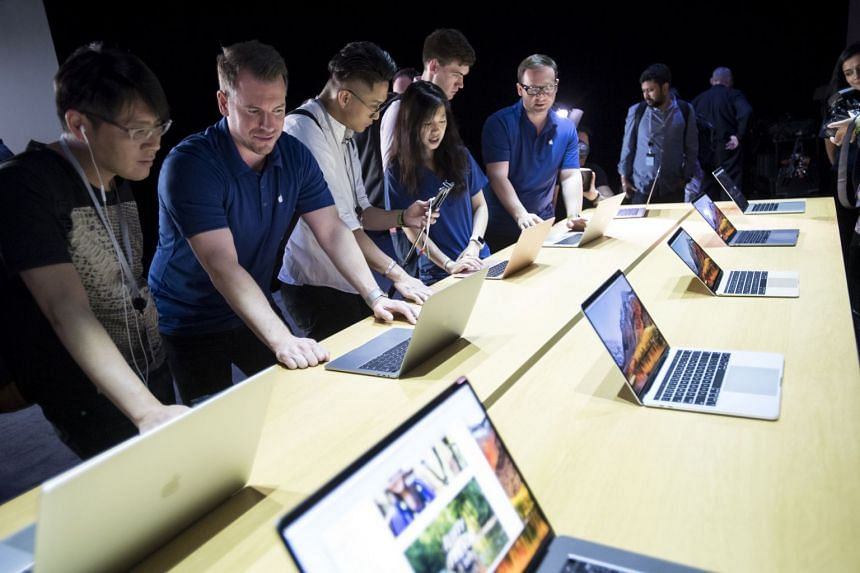 Apple Worldwide Developers Conference attendees checking out MacBook Pro laptops in 2017.