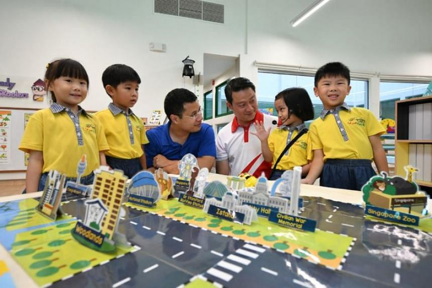 Minister for Social and Family Development Desmond Lee (in blue) and Senior Minister of State for Health and Transport Lam Pin Min interacting with children in front of Bee-Bot, a toy that functions through coding, on July 25, 2018.