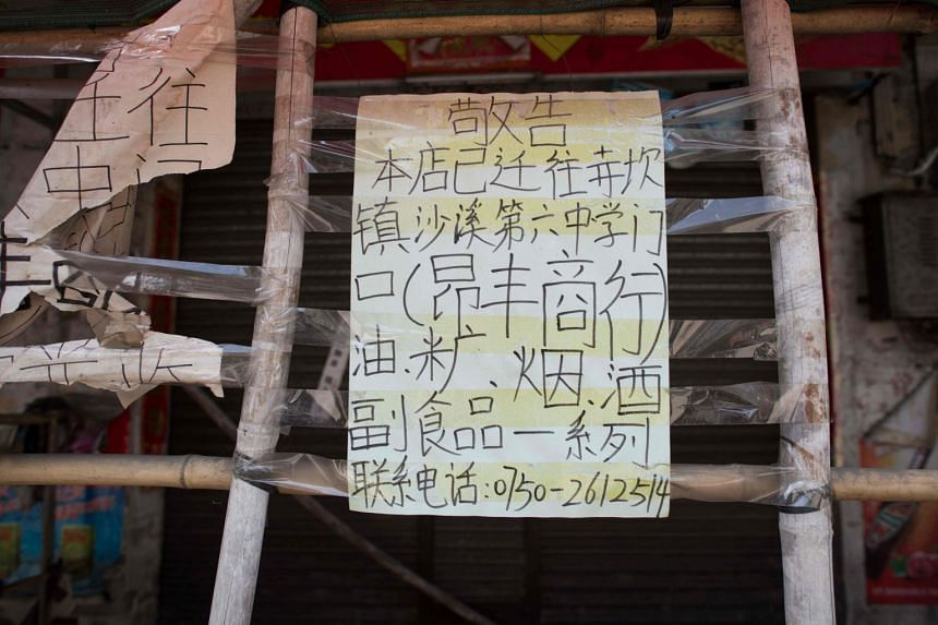 """A sign indicating the new address of a now-closed shop in Chikan village in Kaiping. Several dozen inhabitants are stubbornly holding out against government pressure to sell their properties to make way for a """"heritage"""" theme park."""