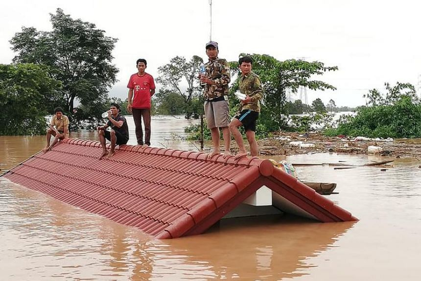 Residents stand on rooftops surrounded by floodwaters in Attapeu province after a dam collapsed on July 23, 2018.