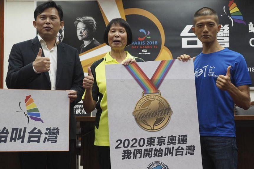 (From left) Lawmaker Huang Kuo-chang, runner Chi Cheng and swimmer You Kun-yi pose at a news conference in Taipei, Taiwan, on July 23, 2018. The group held placards with Chinese and English words saying 'Let Tawian be Taiwan' and 'Start Calling Us Ta