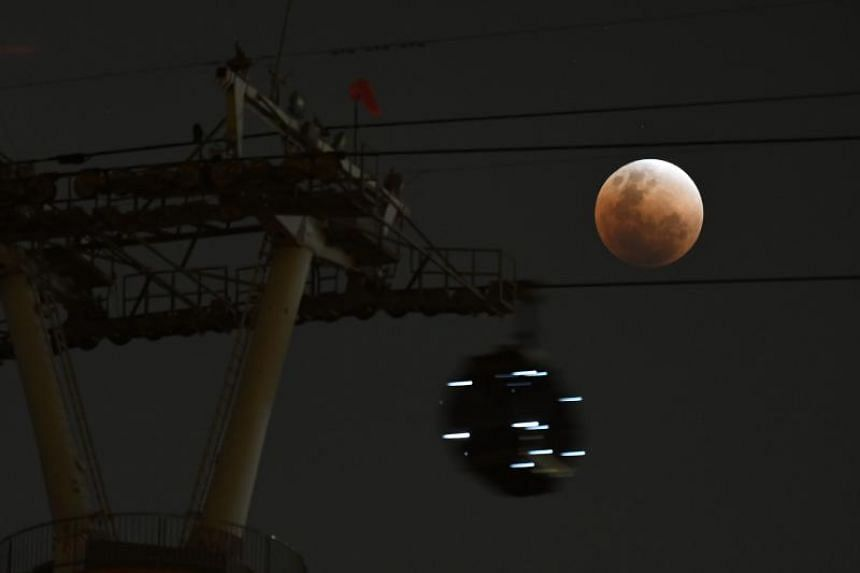 A cable car gondola moves past as the moon is seen during a lunar eclipse, referred to as the super blue blood moon, in Singapore on Jan 31, 2018.