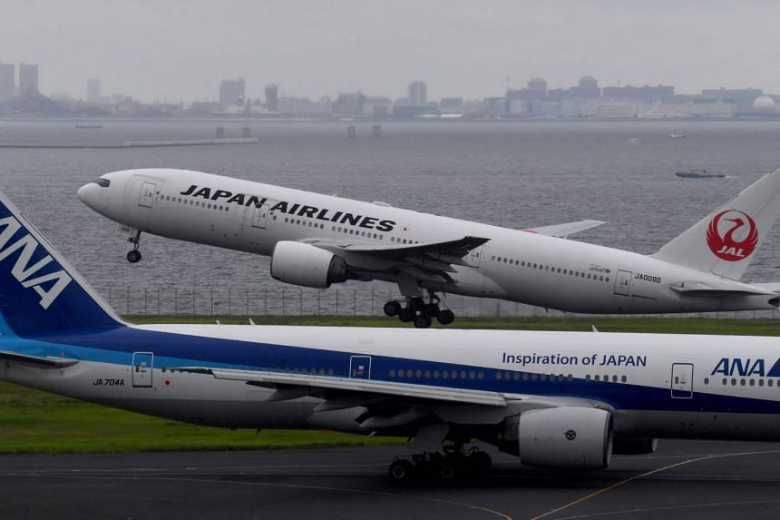 File photo showing a Japan Airlines plane taking off next to an All Nippon Airways plane. Both carriers have escaped a Chinese push to label Taiwan as part of China after removing country labels from all East Asian destinations on their website.