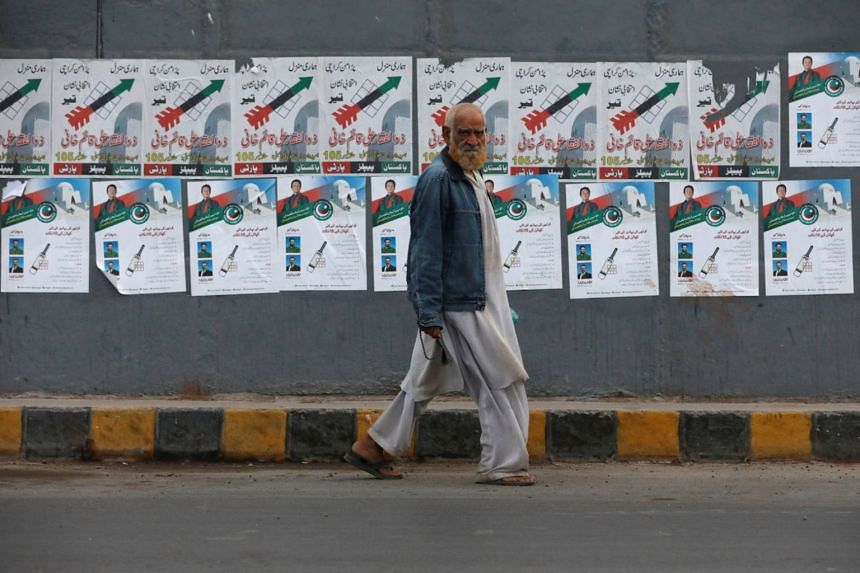 An elderly man walking past a wall with electoral posters in Karachi, Pakistan, on July 25, 2018.