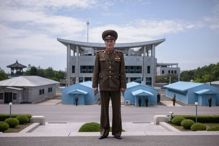 A North Korean soldier poses for a portrait before the military demarcation line at the truce village of Panmunjom within the Demilitarised Zone (DMZ) separating North and South Korea, on June 2, 2018.