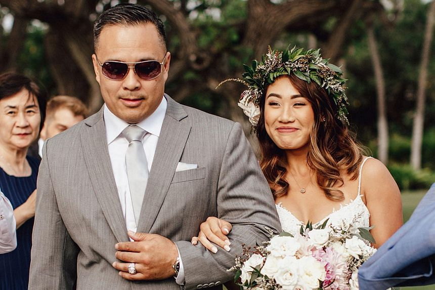 Angela Lee walking with her father Ken during her wedding ceremony.