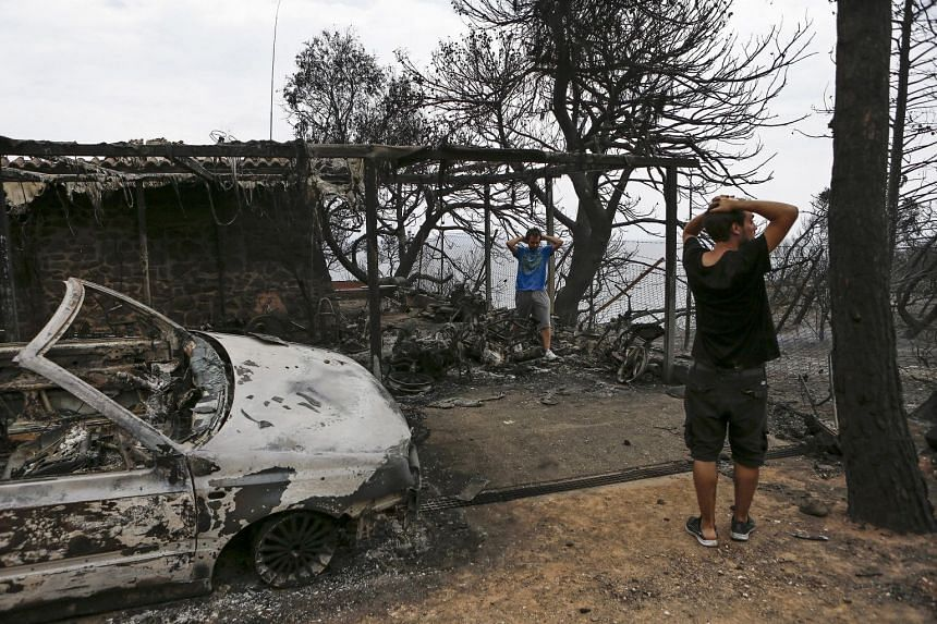 Residents react as they look at their burnt house following wildfires in Mati, near Athens, Greece, on July 24, 2018.
