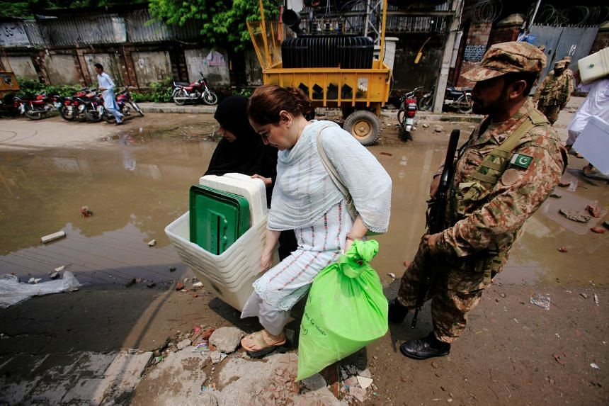 A soldier escorting electoral workers carrying election materials at a distribution point, ahead of the general election, in Lahore, Pakistan, on July 24, 2018.