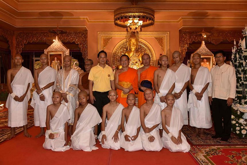 The 11 rescued members of Wild Boars football team, together with their coach and monks, at the Phra That Doi Wao Buddhist temple during an ordination ceremony on July 24, 2018.