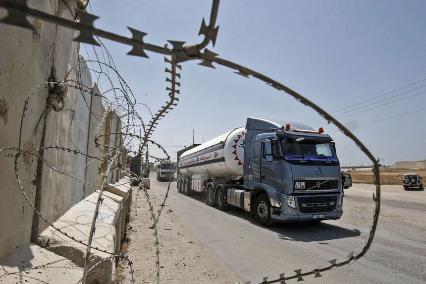 Drivers sit at their trucks at the Kerem Shalom crossing, the main passage point for goods entering Gaza from Israel, following a partial reopening of the crossing point, on July 24, 2018.