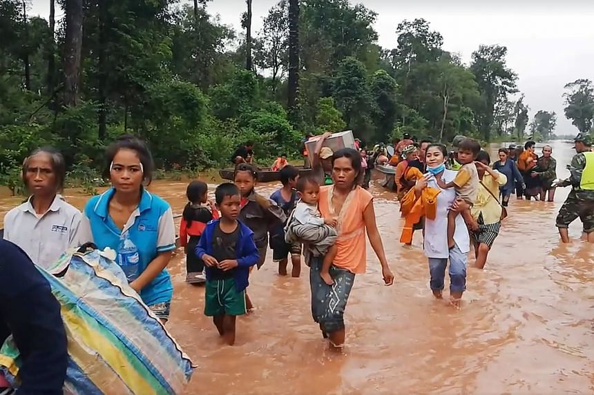 Villagers fleeing the flood waters yesterday following the collapse of the Xe-Pian Xe-Namnoy hydropower dam on Monday in Attapeu province in southern Laos.