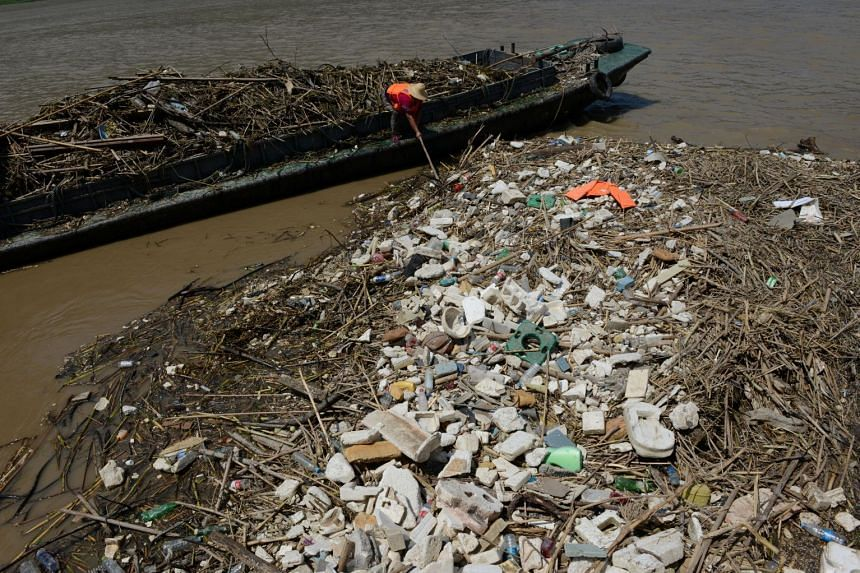 A worker collects garbage left on the bank of Yangtze River after floodwaters receded in Chongqing, China on July 17, 2018.
