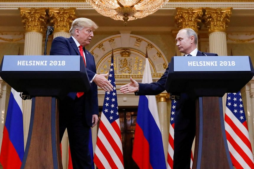Trump and Putin shake hands during a joint news conference after their meeting in Helsinki.