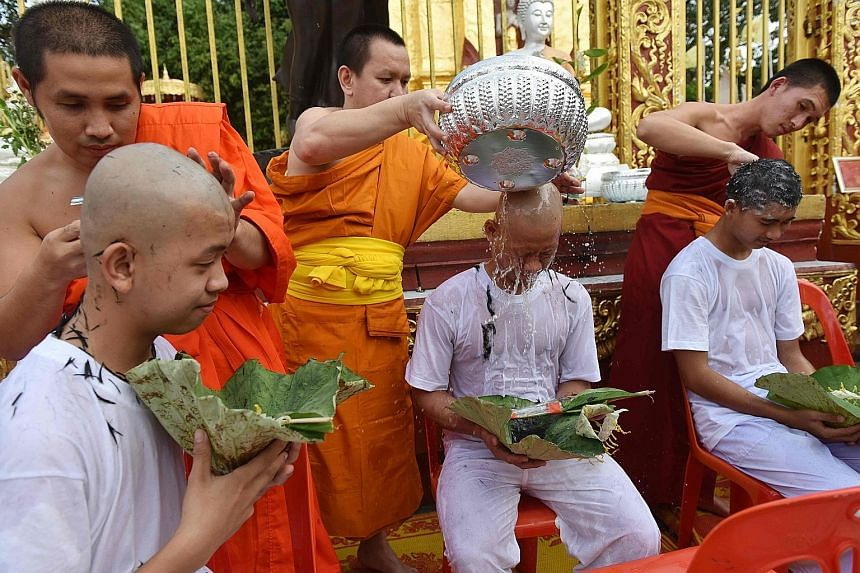 """Buddhist monks shaving the hair of members of the """"Wild Boars"""" football team at a Buddhist temple in the Mae Sai district of Chiang Rai province during a ceremony on Tuesday. Eleven of the 12 boys were ordained yesterday as novice Buddhist monks in m"""