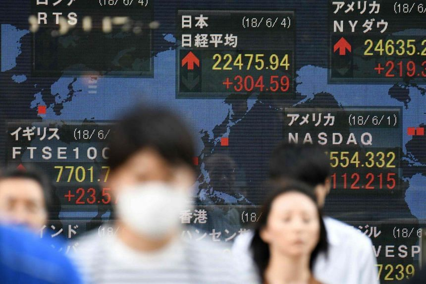 Pedestrians walk in front of an electronics stock indicator in Tokyo, on June 4, 2018.