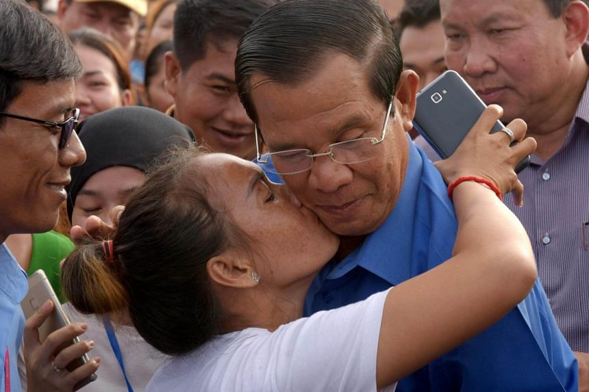 A garment worker kisses Cambodian Prime Minister Hun Sen during an event in Kampong Chhnang province on June 27, 2018.