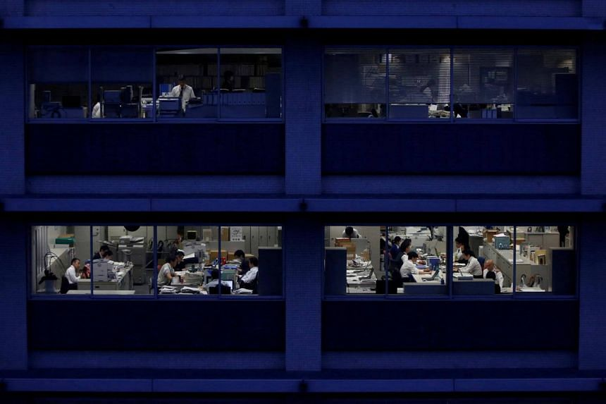 Workers are seen in an office in Tokyo on March 3, 2015.