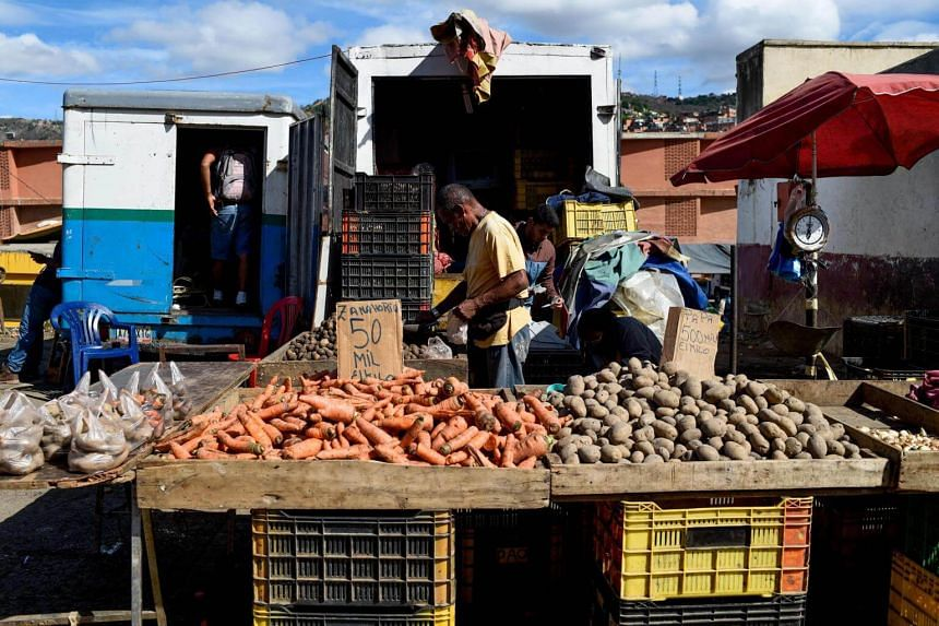 A man buys vegetables in Caracas on June 20, 2018. The International Monetary Fund projected that Venezuela's inflation will skyrocket to 1 million percent by the end of 2018.