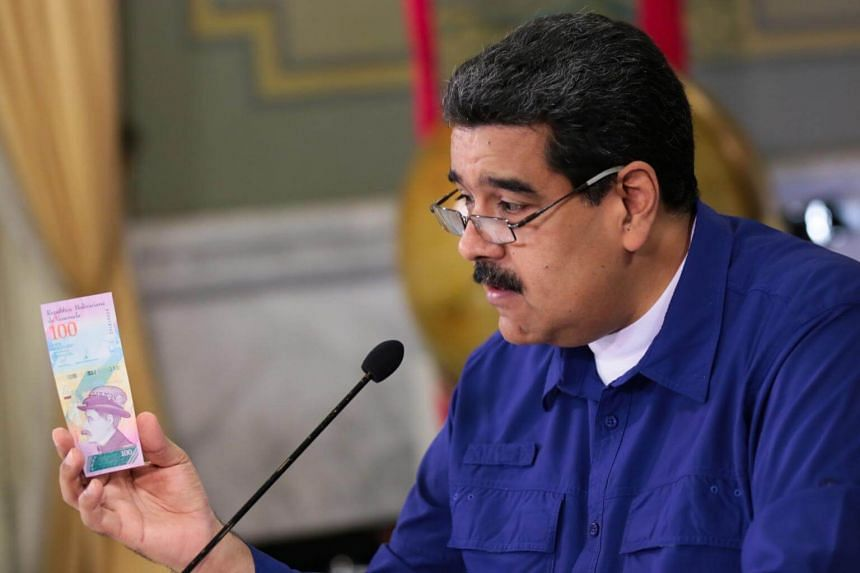 Venezuelan President Nicolas Maduro holds a new bank note as he delivers a statement in Caracas.