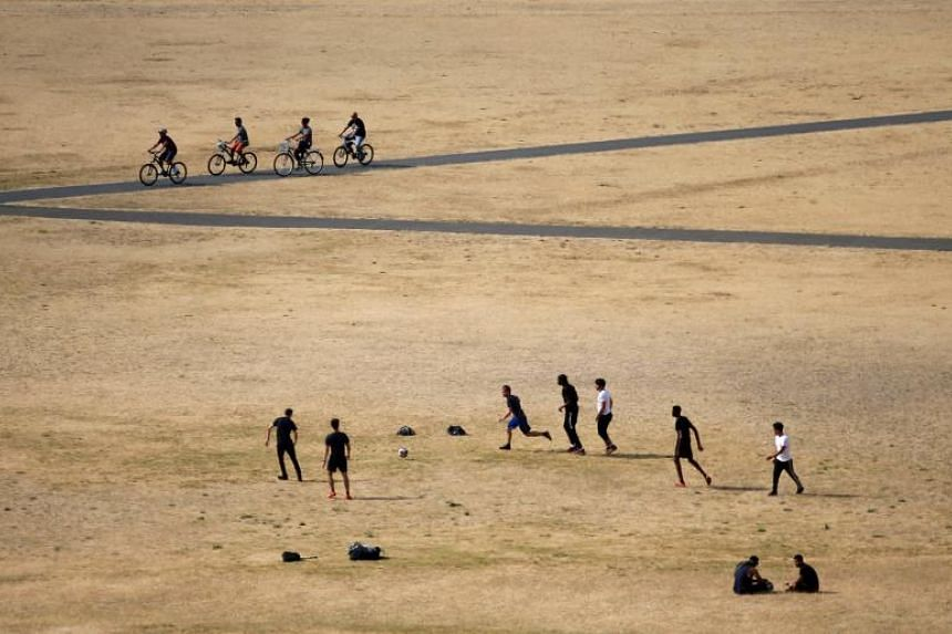 Visitors to Greenwich Park play football on the dry brown grass in London on July 23, 2018.