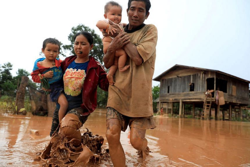 Parents carry their children as they leave their home during the flood after the Xepian-Xe Nam Noy hydropower dam collapsed in Attapeu province, Laos, on July 26, 2018.