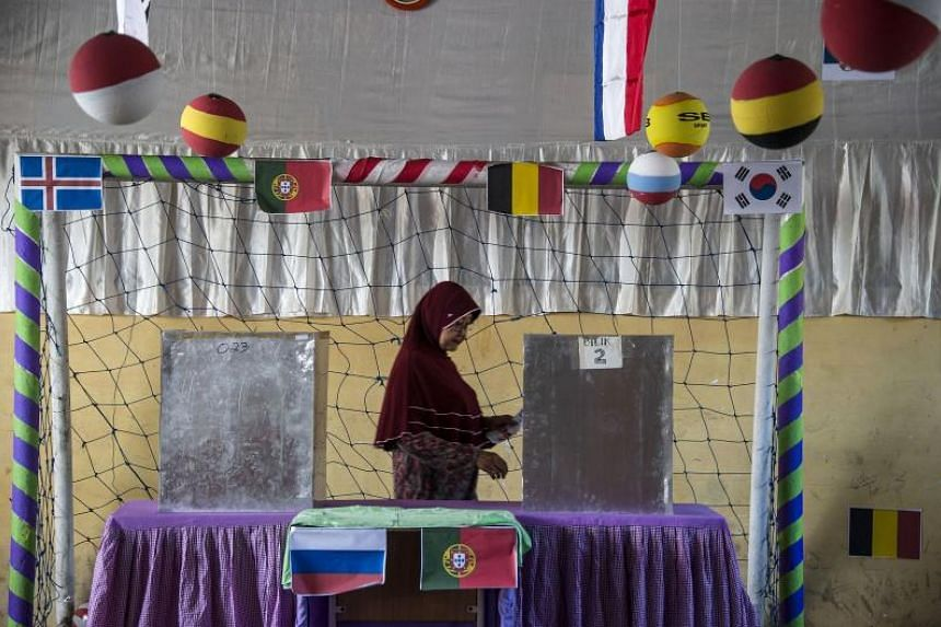 An Indonesian voter casts her ballot at a football-themed polling station decorated to attract voters with the ongoing Russia 2018 World Cup, during regional elections in Surabaya, East Java on June 27, 2018.