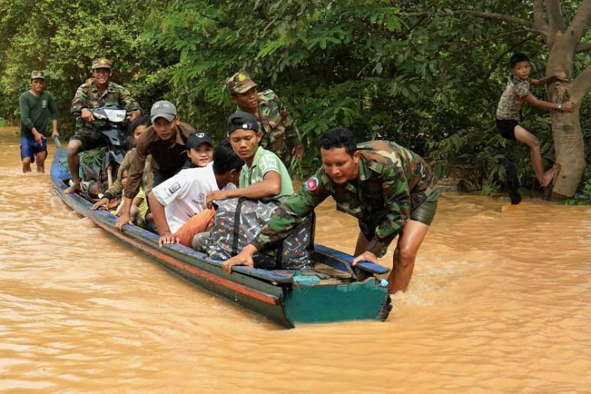 Cambodian soldiers evacuate residents by boat from the flooding in Stung Treng province, on July 26, 2018.